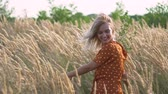 weather : attractive fun hippie blonde woman in the field at sunset having good time outdoors. Slow motion. Female spinning in the field Stock Footage