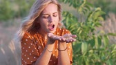 estilo livre : Young blonde woman blowing on hands with golden glitters in the field on sunset. Slow motion