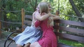 two attractive blonde girlfriends talking and hugging in the park. Sisters have a good time together Stok Video