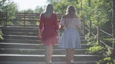 Two attractive beautiful young blond women walk on the steps in the park and are happy on the sunset. Girlfriends in park. Slow motion