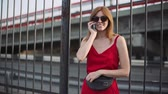 Portrait of attractive young red-haired woman on the street wearing smartphone. Slow motion Stok Video
