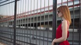 Portrait of attractive young red-haired woman on the street in red dress, having a good time at sunset. Slow motion