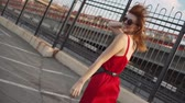 Attractive young red-haired woman running on a street in red dress, having a good time at sunset. Slow motion