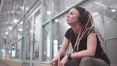 raszta : Beautiful stylish young woman with dreadlocks smoking cigarettes outdoors at night in headphones