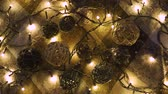 Рождественский подарок : Close-up christmas garland and handmade balls on a playd with golden lights. Christmas concept. Home decor