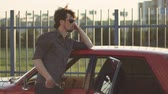 momento : Portrait of a handsome man with his old classic powerful car on the street, at sunset or sunrise Stock Footage