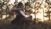 djembe : Beautiful young hippie woman with dreadlocks playing on djembe. Funky woman drumming in nature on an ethnic drum at sunset or sunrise with a human skull Stock Footage