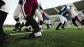 obrana : Low angle view of a football player busting through the line and running