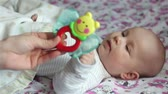 angel : Mother gives baby a toy in the hands of Stock Footage