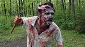 выглядывал : crazy scary zombie standing in the woods and looking for the victim Стоковые видеозаписи