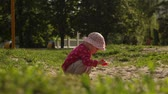 playground : The child plays in the sandbox. Raises the scoop and pours out the sand Stock Footage