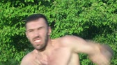 Kickboxer trains blows in front of a big battle. in the park