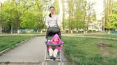 Mom wears a baby girl sitting in a stroller. Walking along the path Wideo