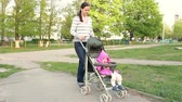 Mom wears a baby girl sitting in a stroller. Walking along the path Dostupné videozáznamy
