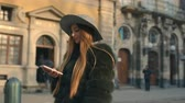 eski moda : Young woman in a gray hat and long hair communicates via smartphone Stok Video