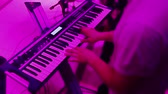 dizgi : Hands playing the piano. Fingers on the piano, colors lights