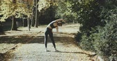 ピラティス : Fitness girl training outdoors in landscape of nature. Fit female working out