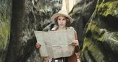 Stylish young traveler girl in hat looking at map, exploring woods Wideo