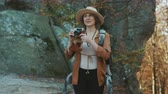 Portrait shot of beautiful young woman in hat taking pictures in the old vintage camera and smiling