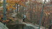 Attractive woman tourist with a backpack on her shoulders travels through autumn forest past the rocks
