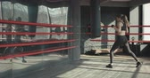 kickboxer : Kickboxing woman in airpods training punching bag in fitness studio fierce strength fit body