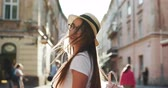 Trendy student in fedora hat, round glasses and hipster backpack. Close up view of Pretty Young Woman Walking like a Model. Looking at the Camera. Wearing Stylish Straw Hat. Having Elegant Make up. Vidéos Libres De Droits