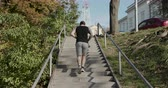 actie : Young man athlete legs running up stairs training intense cardio Workout exercise Male Runner feet jogging on steps in Urban City background
