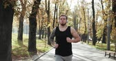 stadt straße : Sport man running in park. Portrait of runner man jogging in park background. Sport workout outdoor. Athlete training run exercise. Attractive young man running wearing earphones
