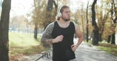 stadt straße : Sport Concept. Athlete Workout For Marathon wearing earphones and listening music. Guy jogging in the park on a background of trees.