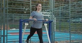 faaliyetler : Exercising on outdoor gym equipment. Woman working out at gym machine. Autumn time outdoors activities. Stok Video