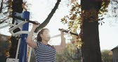 antreman : Women are exercising outdoors with exercise machines. Concept of losing weight with exercise for health. Young girl does chin-up exercise on sports ground in autumn park Stok Video
