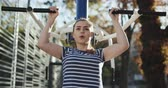 faaliyetler : Young girl does chin-up exercise on sports ground in autumn park. Attractive young muscular girl in sportswear doing pull-ups exercise and chin up. Young Woman Exercising With Fitness Equipment