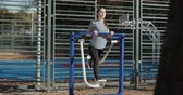 faaliyetler : Sunny morning time, girl perform daily fitness workout. Young sportive woman do walking exercises at outdoor gym, using cross trainer machine. Concept of losing weight with exercise for health