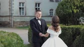 impegno : Wedding couple walking in the park with historic palace. Brunette young stylish woman bride first meeting groom.