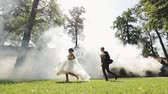 Wedding couple run together in the park. Lovely groom and bride. Happy family. Man and woman in love. Wedding day.
