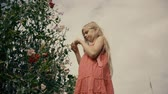 ervilha : cute little girl in a pink polka dot sundress collects with beautiful flowering bush