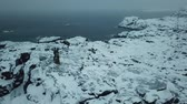 Old lighthouse on the shore of the Barents Sea. Arctic Ocean. Kola Peninsula winter landscape