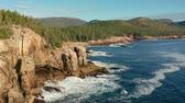 me : Flyover Acadia shore in Maine on a sunny morning with waves crashing on rocky cliffs