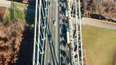 Aerial drone footage of Verrazzano Narrows Bridge, centered above the highway, with view towards Brooklyn (uptilt movement)