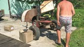 splitting : Khmelnitsky, Ukraine, August 2018: - Man chop wood with a homemade diesel or gasoline unit in the backyard of a farm or a private house. Concept of stocking up of firewood.
