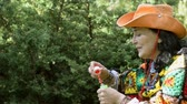 varinha : Adult stylish woman in a cowboy hat and a multicolored poncho blows bubbles in the park outdoors. Concept of active leisure for middle-aged and older people. Vídeos