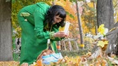 etnia : Beautiful happy woman in green dress photographing yellow leaves in autumn park. Golden autumn concept. Outdoors Close-up. Archivo de Video