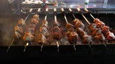 マリネード : Cooking kebabs or barbecue in restaurant or cafe over charcoal. Preparing barbecue with delicious grilled meat on the skewers. Turn over meat on grill.