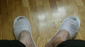 pés : Person bangs his feet, which have disposable slippers at the wooden floor. Fragment feets close-up. High angle view. Vídeos