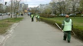 метла : Kiev, Ukraine, April 2019: - Janitors clean the sidewalks on the street in the city.