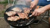 turn over : Grilled food. Meat steak. Man turn over large meat meat steaks, grill on a metal grate. Weekend relaxation concept.