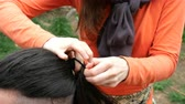 짠 : Woman hairdresser braids young man long hair in a braid. Outdoors Close-up.