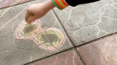 плиты : Child draws a piece of chalk on the paving slab figure digit eight. Стоковые видеозаписи