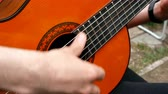 praxe : Performance musician. Acoustic wooden guitar. Outdoors Close-up.