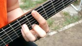 fretboard : Performance musician. Acoustic wooden guitar. Outdoors Close-up.